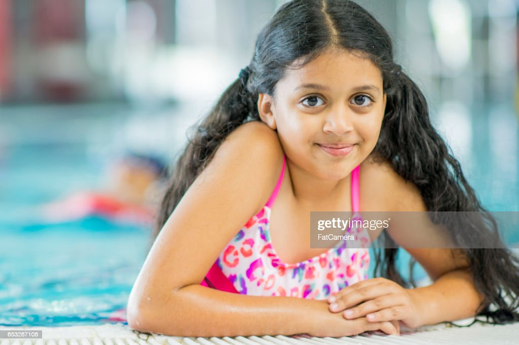 Jong meisje zwemmen aan het zwembad : Stockfoto
