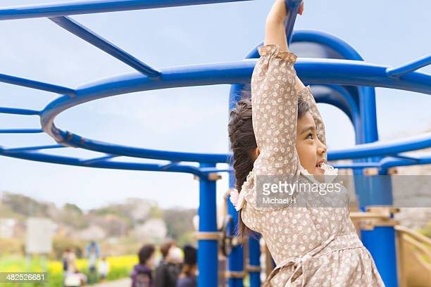 Young girl swinging by monkey bars