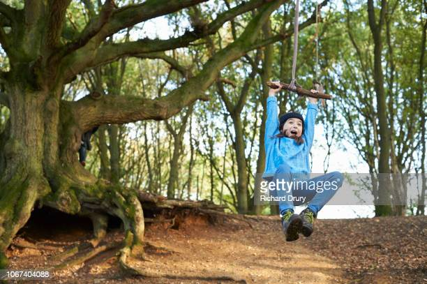 young girl swinging on a rope swing in woodland - woodland stock pictures, royalty-free photos & images