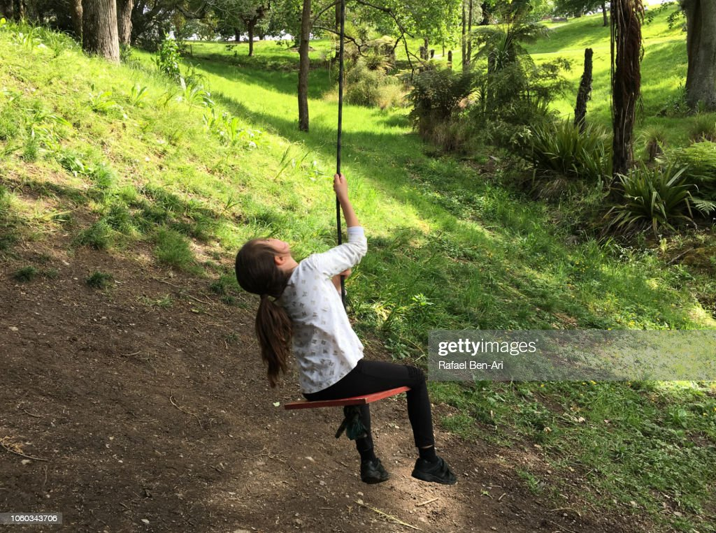 Young Girl Swinging on a Tree Swing : Stock Photo