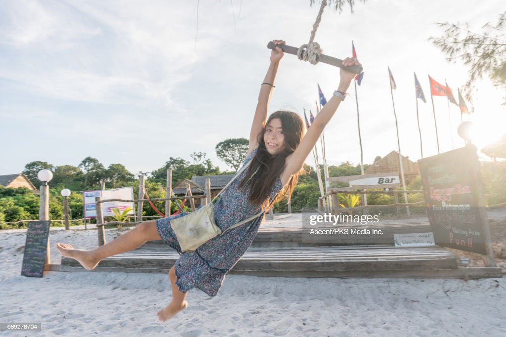 Young girl swings above beach in evening light : Stock Photo
