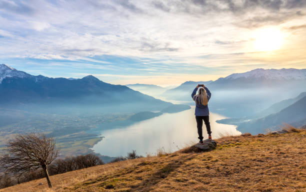 Young girl take a photo with smartphone at sunset above Lake Como