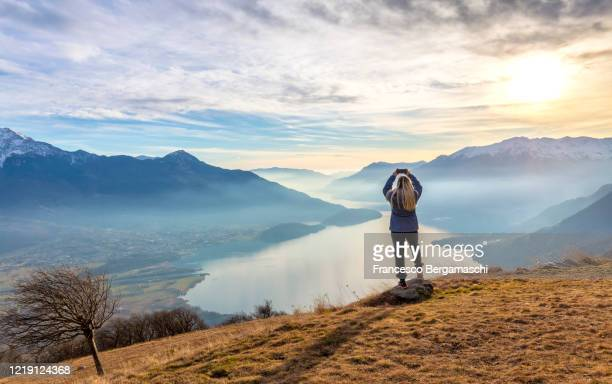young girl take a photo with smartphone at sunset above lake como - italia stock-fotos und bilder