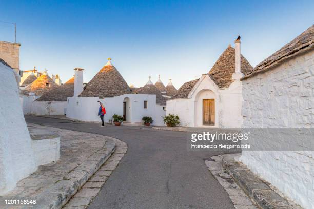 young girl take aphoto with smartphone in the monumental trulli area. - italia stockfoto's en -beelden