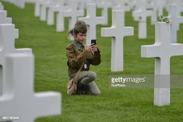 Young girl takes a photo of one of the graves of fallen soldiers at the Normandy American Cemetery that contains the remains of 9,387 American...
