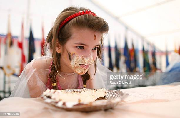 A young girl takes part in a cake eating contest during the Fourth of July festivities at the Baumholder US military base on July 4 2012 in...