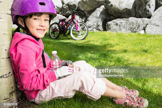 Young girl taking a break while biking in the mountains