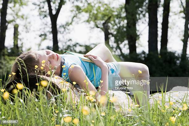 young girl taking a nap on a tree trunk in the countryside