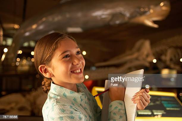 young girl taking notes in a museum - natural history museum stock pictures, royalty-free photos & images