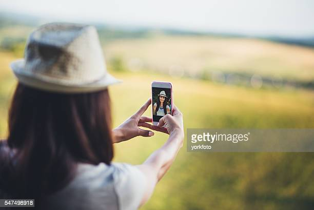 Young girl taking photo with phone in the nature