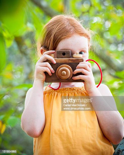 Young girl taking picture with wooden toy camera
