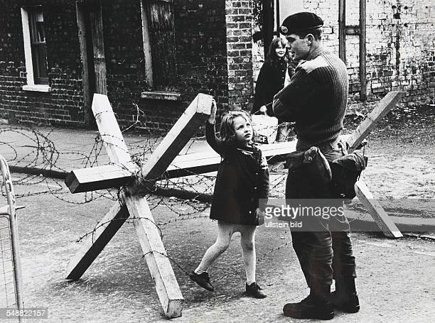 A young girl talking to a British soldier manning a roadblock on a street in Belfast Northern Ireland during The Troubles summer 1973