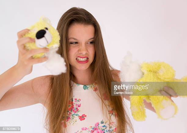 young girl tearing the head off a teddy bear - revenge stock pictures, royalty-free photos & images