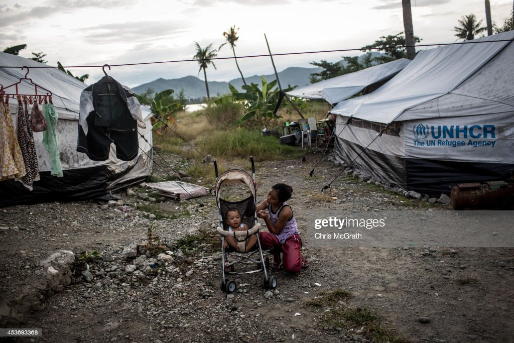 A young girl tends to a baby in the San Jose evacuation complex on August 16, 2014 in Tacloban, Leyte, Philippines. Many families are still housed in temporary tent housing in the San Jose district. The families have been told that they will be rehoused before the visit of Pope Francis. Residents of Tacloban city and the surrounding areas continue to focus on rebuilding their lives nine months after Typhoon Haiyan struck the coast on November 8, 2013, leaving more than 6000 dead and many more homeless. With many businesses and government operations back up and running and with the recent start of the years typhoon season, permanent housing continues to be the main focus with many families still living in temporary accommodation. As well as continuing recovery efforts Leyte is preparing for the arrival of Pope Francis, who will visit the region from January 15- 19.