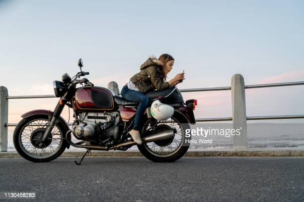 young girl texting sitting back to front on vintage motorcycle - ecchi biker stock pictures, royalty-free photos & images