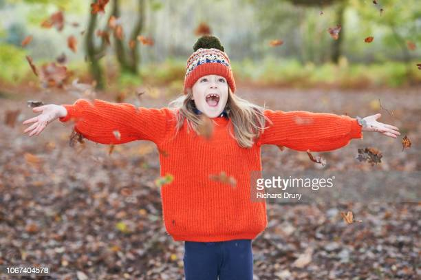 young girl throwing autumn leaves in the air - richard drury stock pictures, royalty-free photos & images