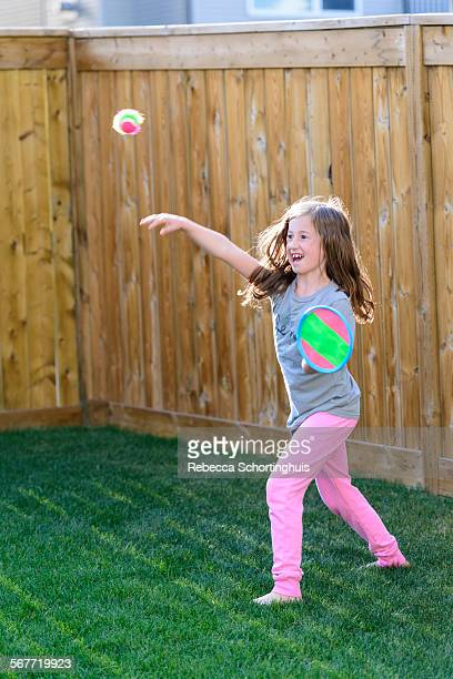 Young girl throwing ball in back yard