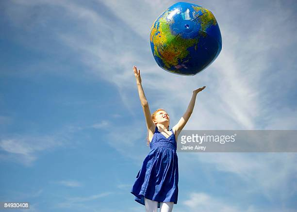 Young girl throwing inflatable globe