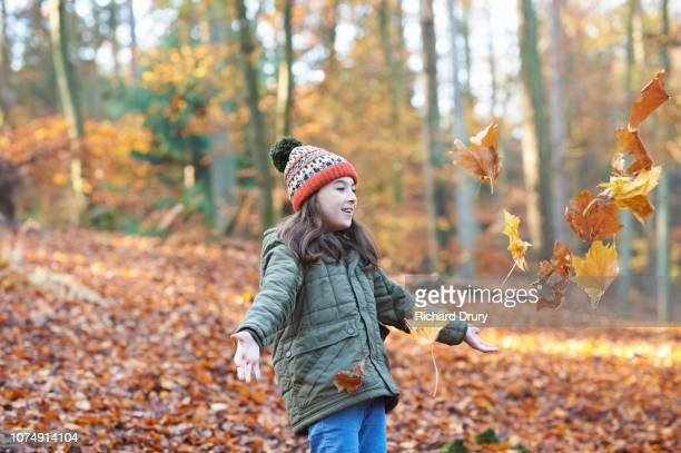 Young girl throwing leaves in the air in Autumnal woodland