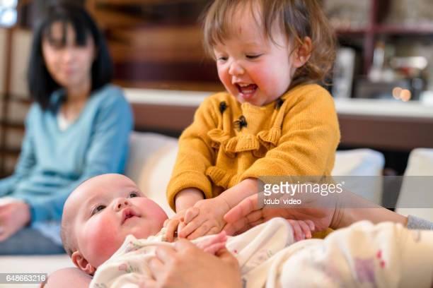 Junges Mädchen kitzeln ihre Babyschwester