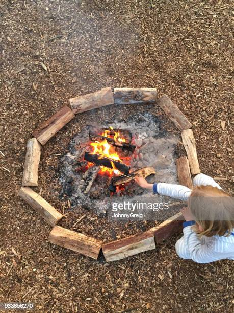 Young girl toasting marshmallow on camp fire