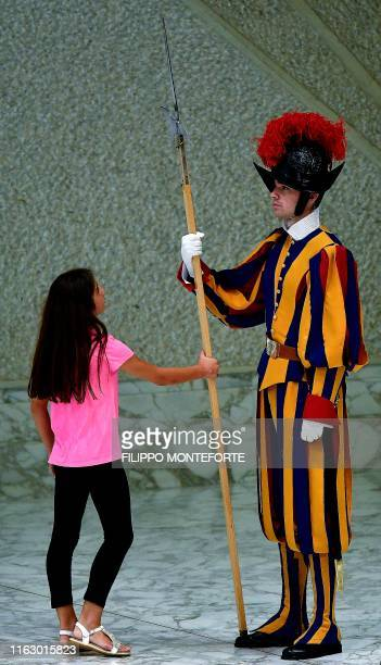 A young girl touches the halberd of a swiss guard as Pope Francis leads his weekly general audience on August 21 2019 at the Vatican