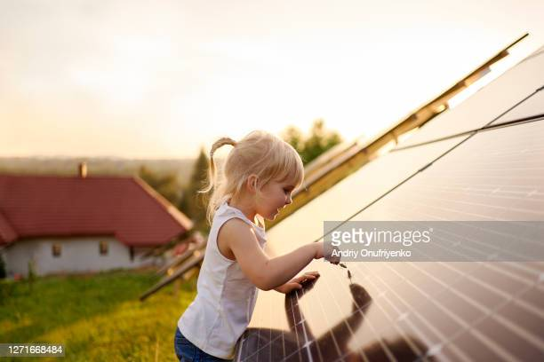 young girl touching solar panel. - positive emotion stock pictures, royalty-free photos & images
