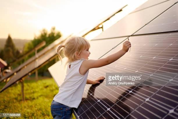 young girl touching solar panel. - rechauffement climatique photos et images de collection