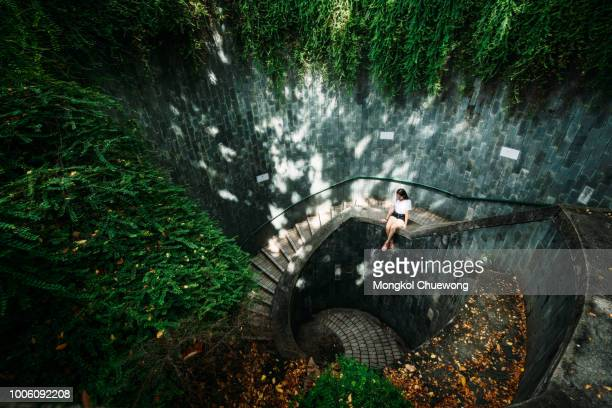 young girl traveler sitting on circle stairs of a spiral staircase of an underground crossing in tunnel at fort canning park, singapore - tropical tree stockfoto's en -beelden
