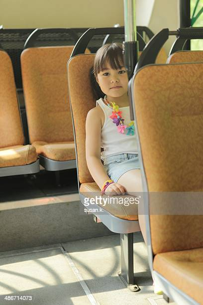 Young girl travelling on public bus herself.