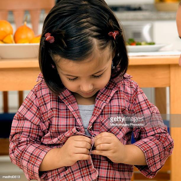 Young girl trying to button her shirt