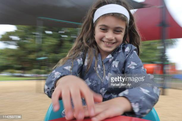 Young girl turning a carousel in the playground