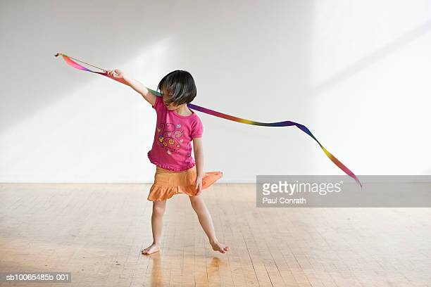 Young girl twirling ribbon in empty room