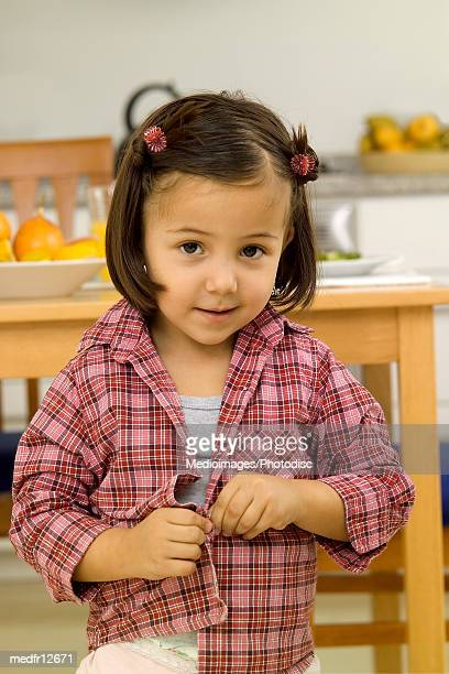 young girl unbottoning plaid shirt - little girl taking off clothes stock photos and pictures