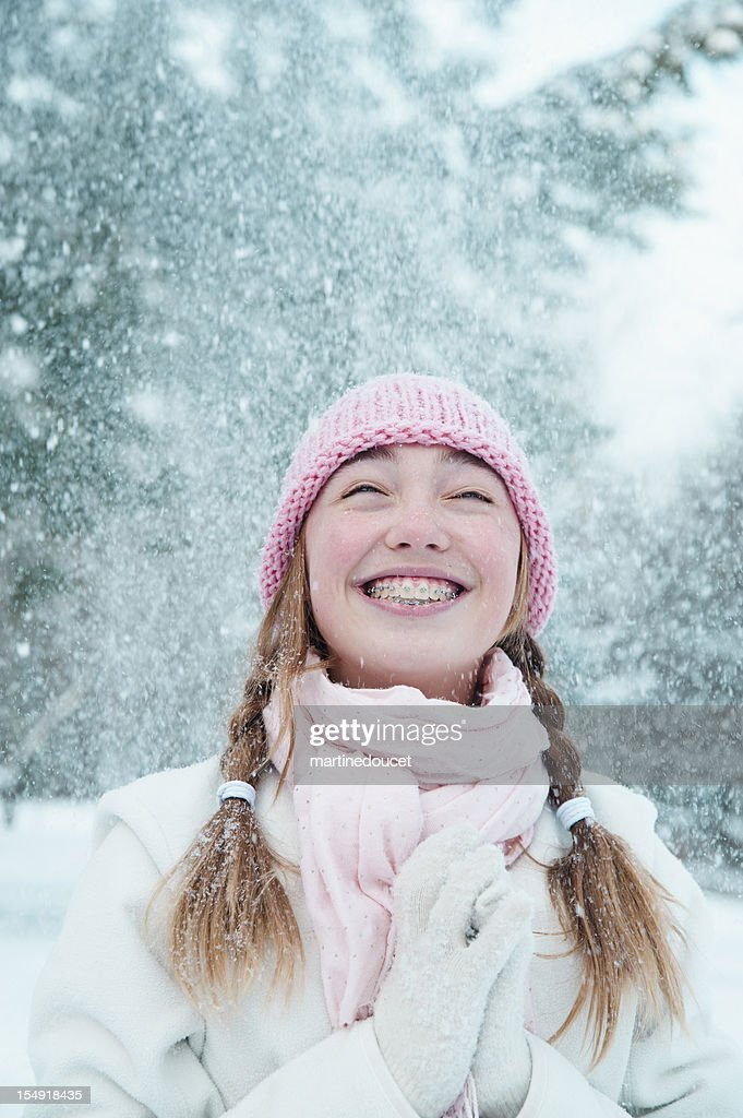 Young girl under falling snow. : Stock Photo