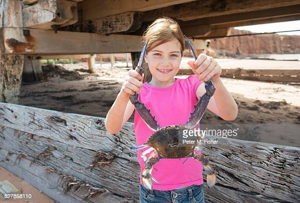 Young girl under jetty with crab