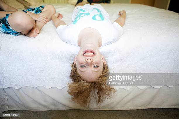 Young girl upside down on bed