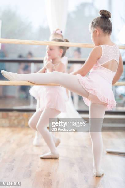 young girl uses ballet barre - little girls dressed up wearing pantyhose stock photos and pictures