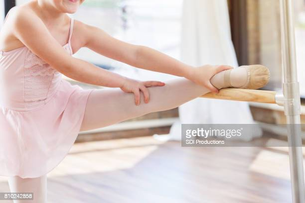 young girl uses ballet barre to stretch her leg before dancing in the studio - little girls dressed up wearing pantyhose stock photos and pictures