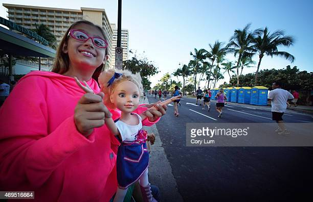 Young girl uses her doll to cheer on runners during The Hapalua Hawaii's Half Marathon on April 12 2015 in Honolulu Hawaii