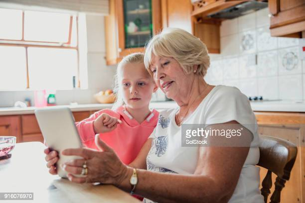 young girl using a digital tablet with her grandmother - british granny stock photos and pictures