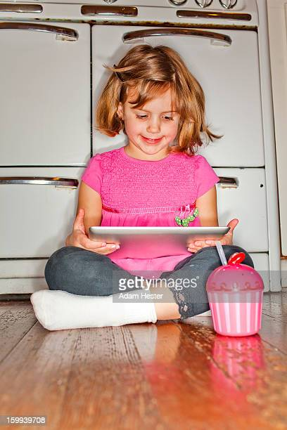 A young girl using a tablet device inside a home.