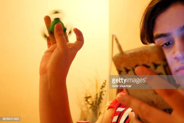a young girl using cell phone and at same time playing and spinning the fidget spinner - punjabi girls images stock photos and pictures
