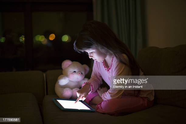 Young girl using digital tablet at night