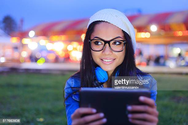 Young girl using digital tablet by night in funfair