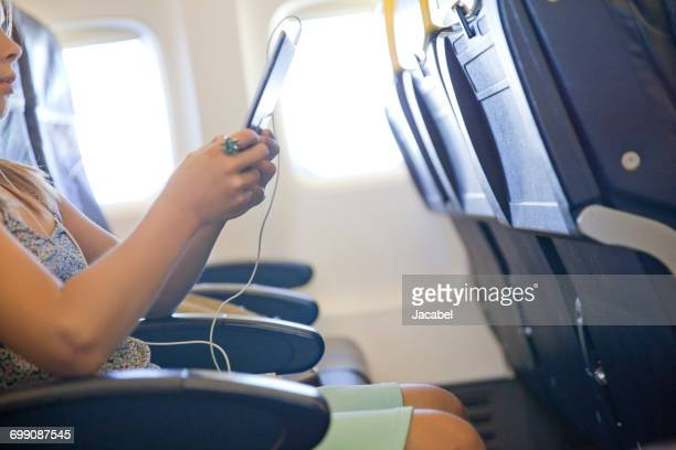 Young girl using digital tablet in airplane