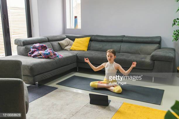 young girl using digital tablet tutorial to exercise at home - exercising stock pictures, royalty-free photos & images