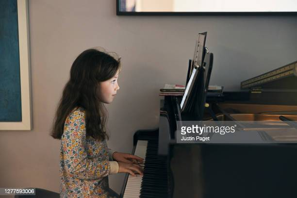 young girl using digital tablet whilst playing piano - keyboard player stock pictures, royalty-free photos & images