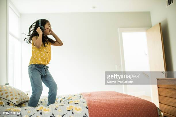 young girl (6 yrs) using headphones and tablet at home - child in bed clothed stock pictures, royalty-free photos & images