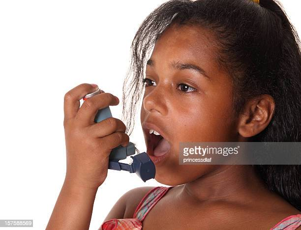 Young girl using her blue inhaler